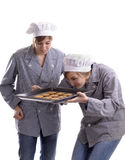 Two young female cooks inspecting cookies Stock Images