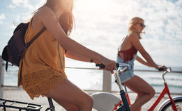 Two young female cycling outdoors on a sunny day Stock Images