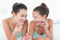Two young female friends applying makeup in bed Royalty Free Stock Image