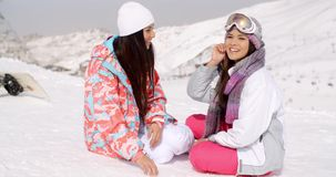 Two young female friends chatting in the snow. Two attractive young female friends sitting chatting in the snow with their snowboards overlooking a snowy valley stock video