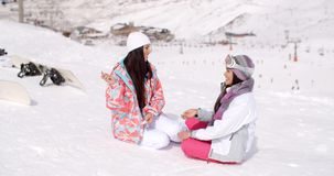 Two young female friends chatting in the snow. Two attractive young female friends sitting chatting in the snow with their snowboards overlooking a snowy valley stock video footage
