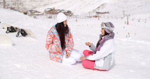 Two young female friends chatting in the snow Royalty Free Stock Images