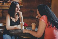 Two young female friends drinking smoothie at cafe stock photo