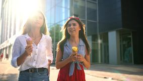 Two young female friends having fun and eating ice cream. Cheerful caucasian women eati icecream outdoors walking in the