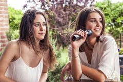 Two young female friends having fun singing a new song. On the microphone Stock Image