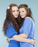 Two young female friends hugging, looking Royalty Free Stock Photo
