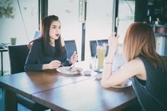 Two young female friends laugh and Having Lunch Together At Rest Royalty Free Stock Photography