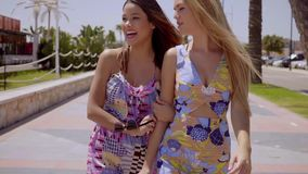 Two young female friends laughing and joking. Two attractive trendy young female friends laughing and joking as they stroll together along a tropical urban stock video footage