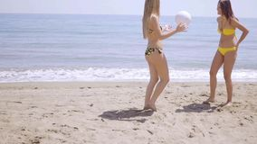 Two young female friends playing beach ball. Two young female friends in bikinis standing playing with a beach ball on a sandy beach overlooking the ocean stock video footage