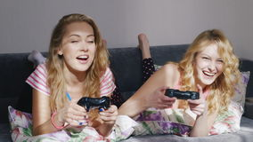 Two young female friends playing on the computer console. Lying on the bed at home in pajamas. HD video stock footage