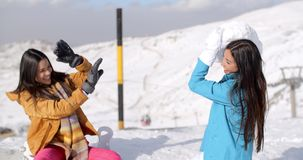 Two young female friends playing in the snow. Threatening to cover one with a large snow ball as she sits on her snowboard in the snow on a mountain summit stock video footage