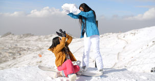 Two young female friends playing in the snow Royalty Free Stock Photos