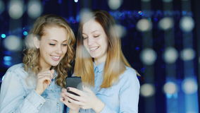 Two young female friends reading message on smartphone in a nightclub stock footage
