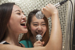 Two young female friends singing into a microphone at karaoke Stock Photo