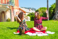 Give me a high five. Two young female friends sitting on an outside green grass park lawn, happy and studying, satisfied with their hard work and giving each royalty free stock images