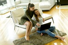Two young female friends sitting in a room on the sofa and using Royalty Free Stock Images
