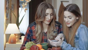 Two young female friends sitting by a table and using phone. stock video
