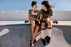 Female friends in skate park laughing and having fun. Two young female friends in skate park laughing and having fun. Women skaters sitting on a ramp with long Royalty Free Stock Photography