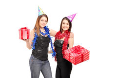 Two young female friends standing close together holdinggifts at Royalty Free Stock Images