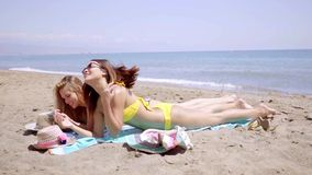 Two young female friends sunbathing in bikinis. On the golden sand of a tropical beach lying side by side at the edge of the sea stock video
