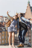Two young female friends taking selfies on a smartphone on the background of the Castle Square in Warsaw Royalty Free Stock Photography