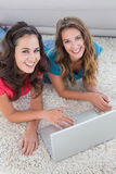 Two young female friends using laptop at home Royalty Free Stock Image