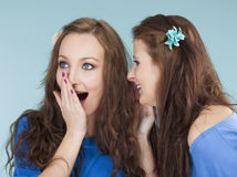 Two young female friends whispering gossip. Isolated on blue royalty free stock images