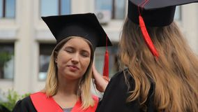 Two young female graduates discussing future plans after graduation ceremony. Stock footage stock footage