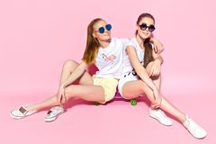 Young women sitting on skateboard stock photos