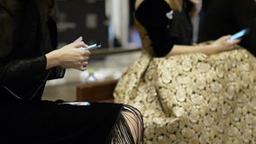 Two young female models in a beautiful dress couture uses the phone on the backstage of fashion week. And people walk past stock footage