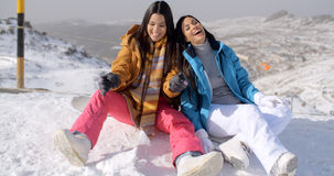 Two young female snowboarders enjoying a chat Stock Photography