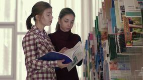 Two young female students focused on choosing books in library stock video footage