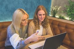 Female friends looking at laptop. Two young female students sitting at the table and working together on laptop Stock Photography