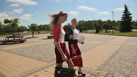 Two young female students walking together outdoors in the park on a sunny day. stock video