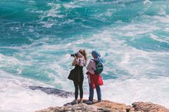Two young female tourists photographing ocean scene from the edge of the rocks. HERMANUS, SOUTH AFRICA - NOVEMBER, 2018: Two young female tourists photographing royalty free stock photo