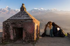 Two young female tourists resting on stone ledge at Sarangkot point of view. Two young female tourists resting on stone ledge next to small stone stupa in the stock photography