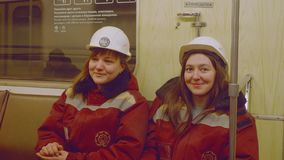 Moscow - circa April, 2018: Two young female workers of metro are in moving train looking at camera and smiling. Two young female workers of metro are in moving stock footage