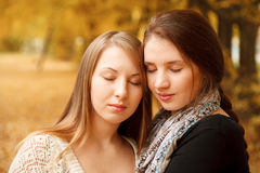 Two young females outdoors. Two young females in autumn forest with eyes closed and heads together Royalty Free Stock Photography