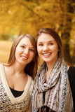Two young females outdoors. Two young females in autumn forest smiling looking away Stock Photography