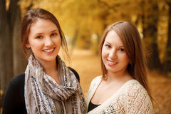 Two young females outdoors. Two young females in autumn forest smiling looking at camera Stock Images