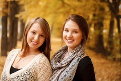 Two young females outdoors. Two young females in autumn forest smiling looking at camera Royalty Free Stock Images