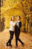 Two young females outdoors. Two young females in autumn forest smiling looking at camera full length shot Royalty Free Stock Images