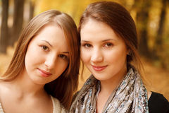 Two young females outdoors. Closeup of two young females in autumn forest looking at camera Royalty Free Stock Image