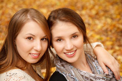 Two young females outdoors. Closeup of two young females in autumn forest sitting looking at camera Stock Images