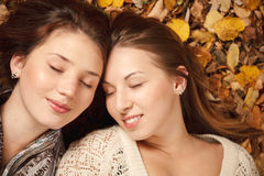 Two young females outdoors. Closeup of two young females lying down in autumn forest with eyes closed Royalty Free Stock Photo