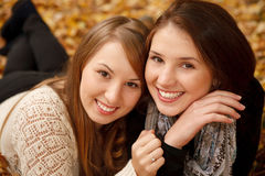 Two young females outdoors. Closeup of  two young females lying down in autumn forest smiling looking at camera Royalty Free Stock Photos