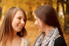 Two young females outdoors. Closeup of two young females talking in autumn forest smiling Stock Photos