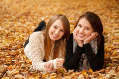 Two young females outdoors. Two young females lying down in autumn forest smiling looking at camera Royalty Free Stock Photography