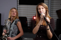 Two young females sign the song Stock Images