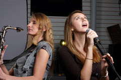 Two young females sign the song Royalty Free Stock Photography